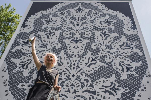 Kiskunhalas, 2015. május 20. NeSpoon lengyel street art mûvész az általa készített halasi csipkét ábrázoló óriásfestmény elõtt Kiskunhalason 2015. május 20-án. A mûvész világszerte csipkével dekorálja a városokat. A halasi csipkét a Csipkeház melletti emeletes ház falára festette. MTI Fotó: Ujvári Sándor